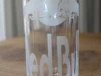 Redbull logo gezandstraald op glas.