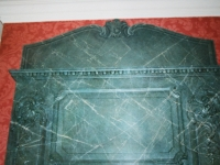 Bovenste deel van  schouw beschilderd om contact te krijgen met het plafond. Beschildert als vert de mer marmer. De profielen zijn geschilderd als tromp l`oeil.