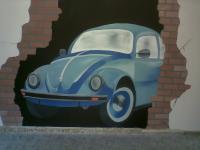 Volkswagen kever `door de muur` op muur beschilderd