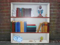 Trompe l`oeil boekenkast geschilderd op paneel met voorwerpen passen bij de bewoner