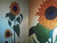 Zonnebloem op muur geschilderd.